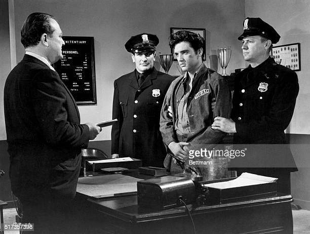 Elvis Presley is held by guards Carl Sax and Hubi Kearns as Warden Hugh Sanders prepares to sentence Elvis for creating a disturbance in prison in a...