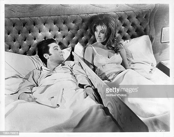 Elvis Presley lies in bed with Michele Carey in a scene from the film 'Live A Little Love A Little' 1968