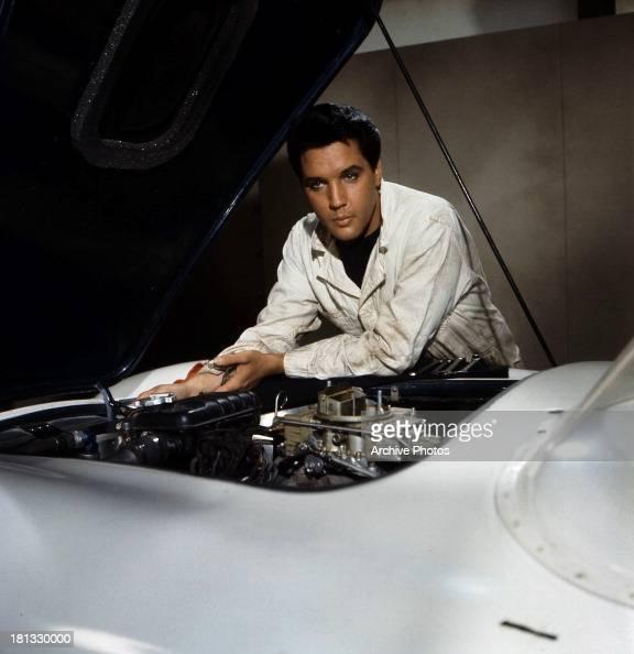 Elvis Presley Looks Under The Hood Of His Car In A Scene