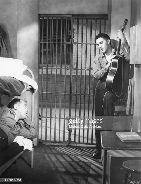 Elvis Presley plays a Gibson acoustic guitar in a scene from the movie Jailhouse Rock which was released in 1957