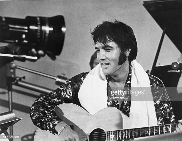 Elvis Presley plays guitar during a scene from the documentary film Elvis That's the Way It Is