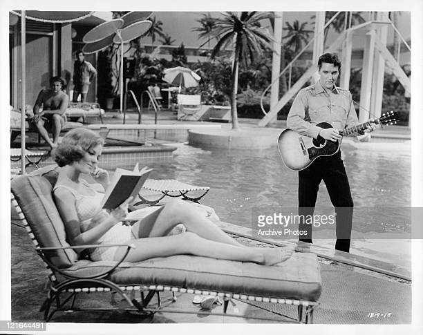 Elvis Presley plays the guitar for Mary Ann Mobley while she reads a book in a scene from the film 'Girl Happy' 1965