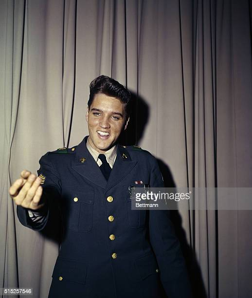Elvis Presley poses for photographers in uniform after concluding his 18 month tour of duty with the army in Germany