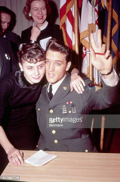 Elvis Presley prepares to signs an autograph and receives a hug from a fan after his return to the United States. Elvis completed an 18 month tour of...
