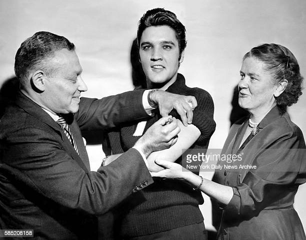 Elvis Presley receiving a polio vaccination from Dr. Leona Baumgartner and Dr. Harold Fuerst at CBS studio 50 in New York City.