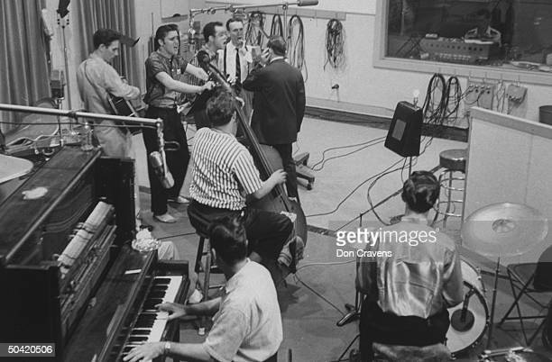 Elvis Presley recording a new song in an unident recording studio backed up by the Jordanaires vocally Bill Black on bass and DJ Fontana on drums