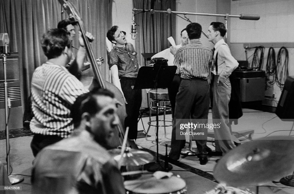 Elvis Presley recording a new song in an unident. recording studio, backed up by the Jordanaires vocally (made up of Gordon Stoker, Neal Matthews, Jr., Hoyt Hawkins and Hugh Jarrett), Bill Black on bass and D.J. Fontana on drums.