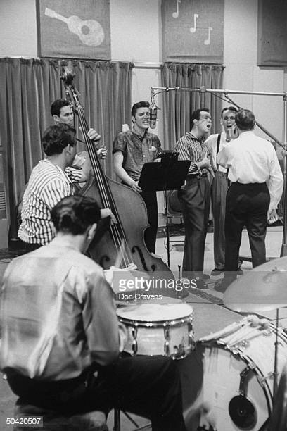 Elvis Presley recording a new song in an unidentified recording studio backed up by the Jordanaires vocally made up of Gordon Stoker Neal Matthews Jr...