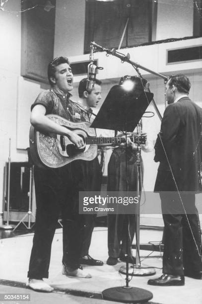 Elvis Presley recording song in Nashville studio agonizing expression on face wearing sport shirt holding guitar singing new song after his record...