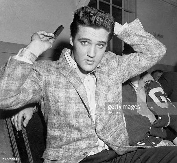 Elvis Presley runs a comb through his famous tresses at the Draftee Receiving Depot here on March 24th. The songster is scheduled for a trip to the...