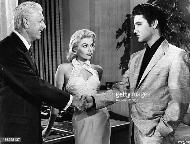 Elvis Presley shakes hands with an unknown actor in a scene from the film 'Jailhouse Rock' 1957