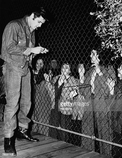 Elvis Presley signing autographs for his fans who are kept at bay by a wire fence