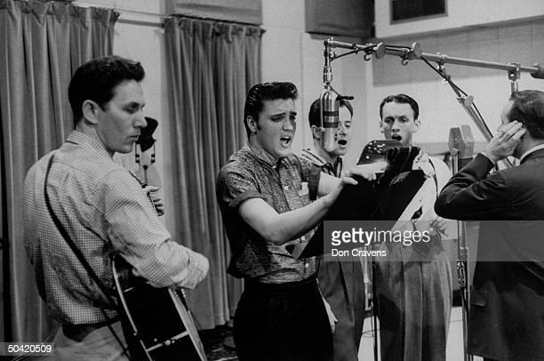 Elvis Presley singing expressively while recording a new song in an unidentified recording studio backed up by the Jordanaires made up of Gordon...