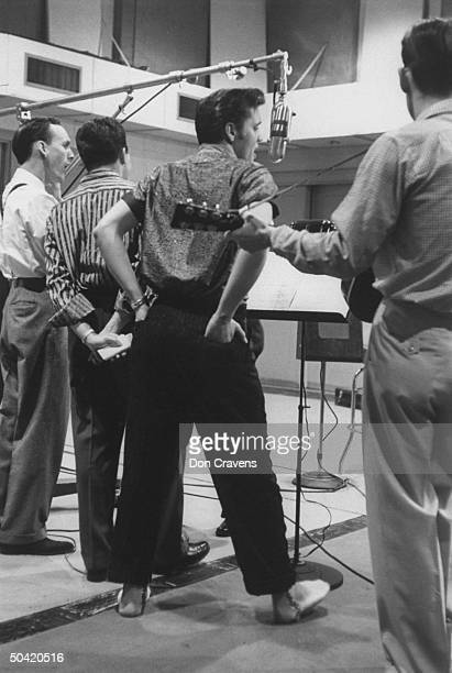 Elvis Presley singing expressively with hands in back pockets while recording a new song in an unidentified recording studio backed up by the...