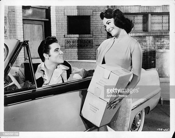 Elvis Presley sitting in the driver's seat of a convertible car smiling at Judy Tyler as she smiles back in a scene from the film 'Jailhouse Rock'...