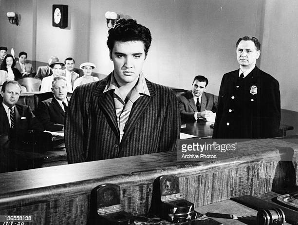 Elvis Presley stands in a courthouse in a scene from the film 'Jailhouse Rock' 1957