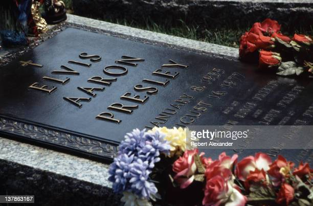 Elvis Presley's grave is a popular attraction at the late singer's 'Graceland' estate in Memphis Tennessee Visitors leave an assortment of flowers...