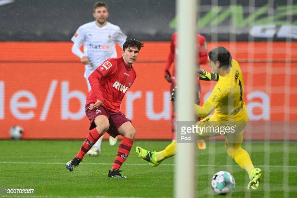 Elvis Rexhbecaj of 1. FC Koeln scores his team's second goal past Yann Sommer of Borussia Moenchengladbach during the Bundesliga match between...