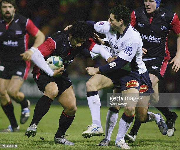 Elvis Sevealaii of Sale Sharks is tackled by Nicolas Raffault of Castres during the Heineken Cup match between Sale Sharks and Castres Olympique at...