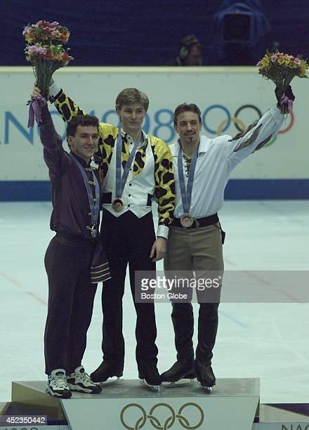 Elvis Stojko Ilya Kulik and Philippe Candeloro hold flowers aloft during the Olympic medal ceremony following the men's long skating program Kulik...