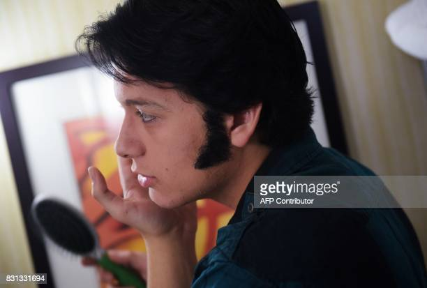 Elvis tribute artist Matthew Boyce puts on sideburns in his hotel room as he prepares for the 'Ïmages of the King' contest on August 12 2017 in...