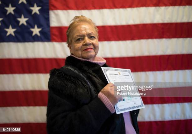 Ely Carlota Ferraro originally from Ecuador stands for a picture with her Certificate of Naturalization during a ceremony for new US citizens...