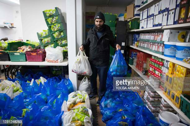 Elyas Ismail, founder of the Newham Community Project food bank, organises food packages ahead of their collection by international students, in east...