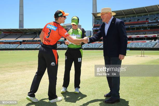 Elyse Villani of the Scorchers and Alex Blackwell of the Thunder greet match referee Ian Thomas before the coin toss during the Women's Big Bash...