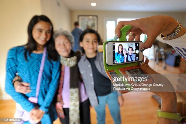 Elyzabeth Luu takes a picture of her niece and nephew, Tasha and Hendrix Zentil, with her grandmother, Chinh Le during a family get-together in...