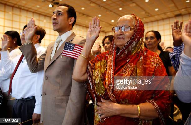 Emad Mesdary originally of Egypt left and Momtaz Begum originally of Bangladesh right raise their right hands and take the oath of citizenship during...