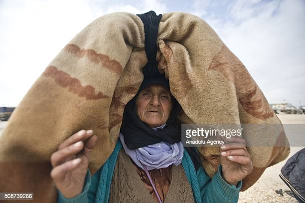 Eman Ali a Syrian woman who fled bombing in Aleppo carries her belongings on her head at the Oncupinar crossing opposite the Turkish province of...