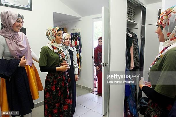 Eman Elnachar and Sara Elmir assist Aula Dbouk at Sara Elmir's home clothing studio on December 4 2014 in Bankstown Australia Sara Elmir 26 and...