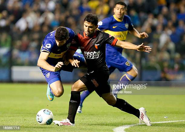 Emanuel Gigliotti of Boca Juniors fights for the ball with Oscar Carnielo of Colon during a match between Boca Juniors and Colon as part of the 13th...