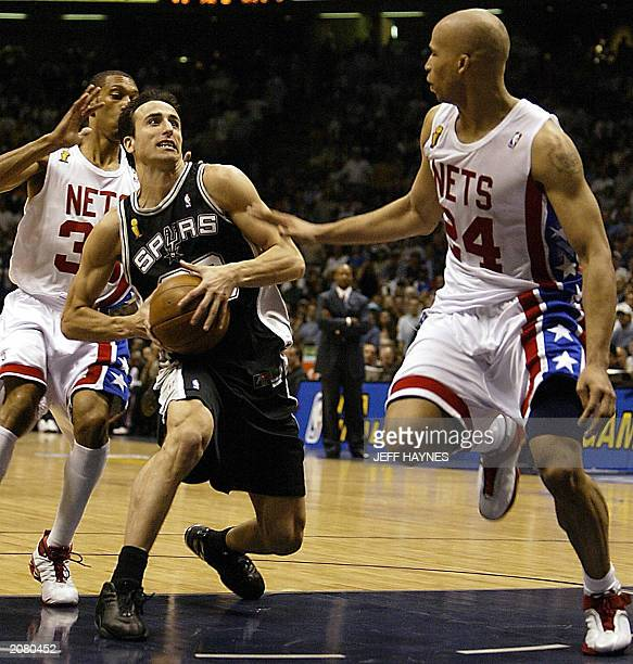 Emanuel Ginobili of the San Antonio Spurs drives to the basket past Kerry Kittles and Richard Jefferson of the New Jersey Nets during the second half...