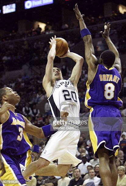 Emanuel Ginobili of the San Antonio Spurs goes up for a shot between Kobe Bryant and Devean George of the Los Angeles Lakers during Game one of the...