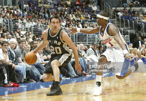 Emanuel Ginobili of the San Antonio Spurs looks to pass under pressure from Keyon Dooling of the Los Angeles Clippers on April 11 2004 at Staples...