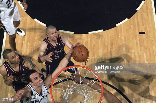 Emanuel Ginobili of the San Antonio Spurs rebounds over Jason Kidd and  Kenyon Martin of the. The New Jersey Nets ... d07e7ef9d
