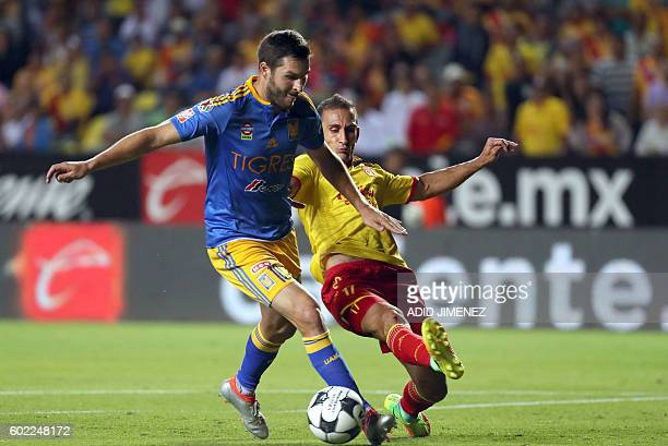 Emanuel Loeschbor of Morelia vies for the ball with Andre Pierre Gignac of Tigres during their Mexican Apertura 2016 tournament football match at the...