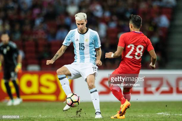Emanuel Mammana of Argentina fights for the ball with Hafiz Sujad of Singapore during the International Test match between Argentina and Singapore at...