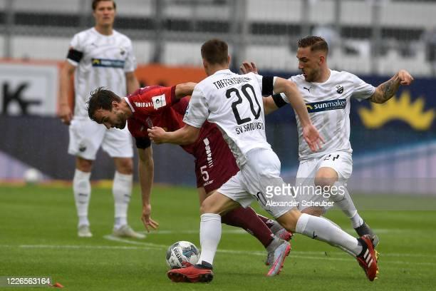 Emanuel Taffertshofer and Robin Scheu of Sandhausen challenge Benedikt Gimber of Regensburg during the Second Bundesliga match between SV Sandhausen...