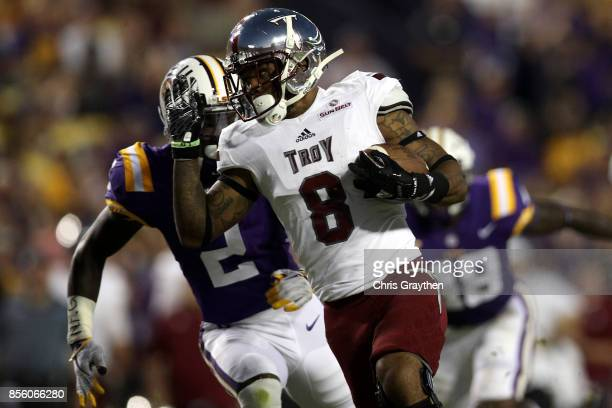 Emanuel Thompson of the Troy Trojans avoids a tackle by Kevin Toliver II of the LSU Tigers at Tiger Stadium on September 30 2017 in Baton Rouge...