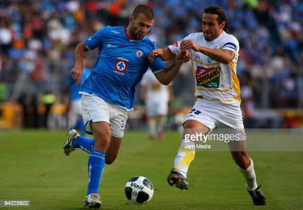 Emanuel Villa of Cruz Azul vies for the ball with Mauricio Romero of Morelia during their semifinals match as part of the 2009 Opening tournament in...