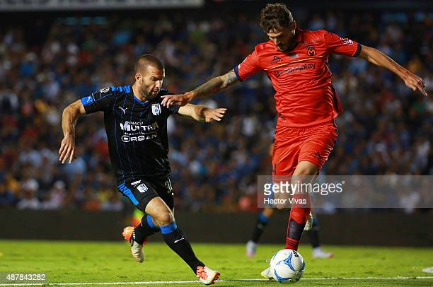 Emanuel Villa of Queretaro fights for the ball with Marco Torsiglieri of Morelia during a 8th round match between Queretaro and Morelia as part of...
