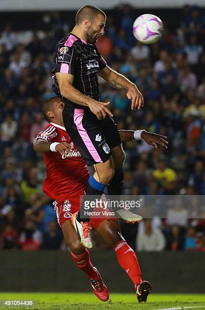 Emanuel Villa of Queretaro heads the ball over Leiton Jimenez of Tijuana during the 12th round match between Queretaro and Tijuana as part of the...
