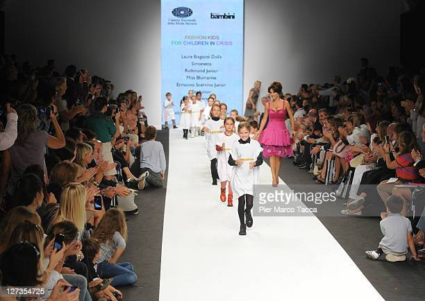 Emanuela Folliero and some young girls and boys walk the runway at the Fashion Kids For Children In Crisis Spring/Summer 2012 fashion show as part...