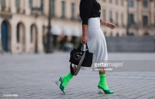 Emanuela wearing a Studio Luxain sweater, a white skirt, a prada bag, balenciaga socks and zara heels on October 02, 2021 in Paris, France.