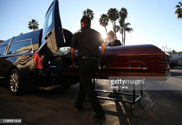 Embalmer and funeral director Kristy Oliver and funeral attendant Sam Deras load the casket of a person who died after contracting COVID-19 into a...