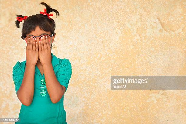 Embarassed, guilty, nervous little girl with hands covering face.