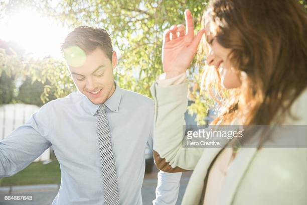 Embarrassed flirty young businesswoman and man on sunlit street