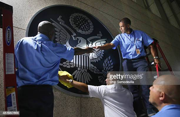 S Embassy employees clean the seal of the United States after hanging it on the outside of the building a few hours before the ceremonial flagraising...